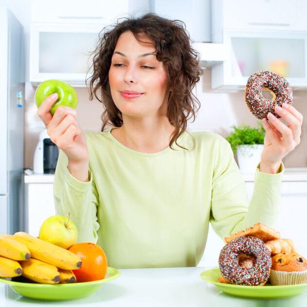 Visar kvinna som väljer mellan nyttig och onyttig mat